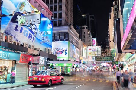 sq: HONG KONG, CHINA - APR 23: Crowded street view at night on April 23, 2012 in Hong Kong, China. With 7M population and land mass of 1104 sq km, it is one of the most dense areas in the world.