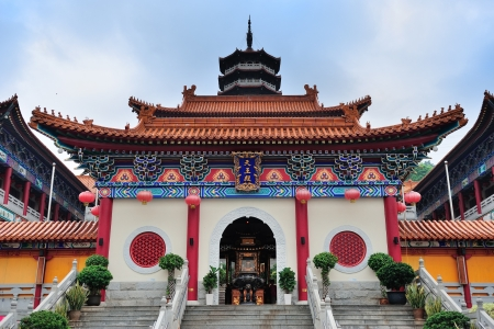Chinese temple in Hong Kong with pagoda style architecture and tower.