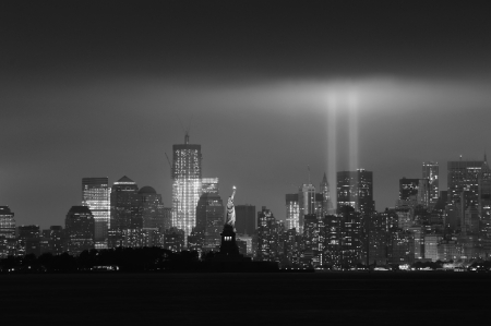 september 11: New York City Manhattan downtown skyline black and white at night with statue of liberty and light beams in memory of September 11 viewed from New Jersey waterfront