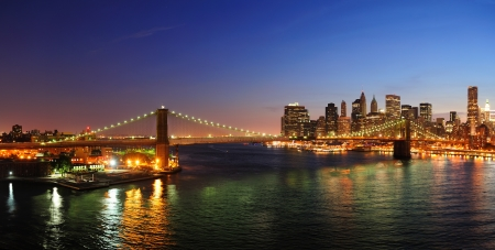 New York City Manhattan downtown skyline aerial view at dusk with skyscrapers lit over East River with reflections