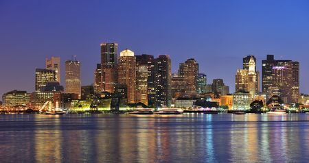 Boston downtown skyline panorama with skyscrapers over water with reflections at dusk illuminated with lights