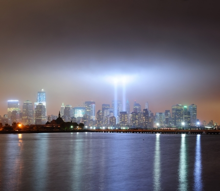 september 11: New York City Manhattan downtown skyline at night from Liberty Park with light beams in memory of September 11 viewed from New Jersey waterfront