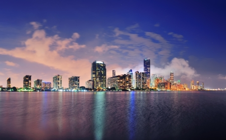 city of miami: Miami city skyline panorama at dusk with urban skyscrapers over sea with reflection Editorial