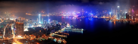 Victoria Harbor aerial view with Hong Kong skyline and urban skyscrapers at night