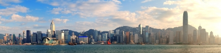harbors: Hong Kong Victoria Harbor in afternoon with urban city skyline and colorful cloud Stock Photo