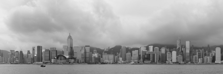 Urban architecture in Hong Kong Victoria Harbor with city skyline and cloud in the day in black and white