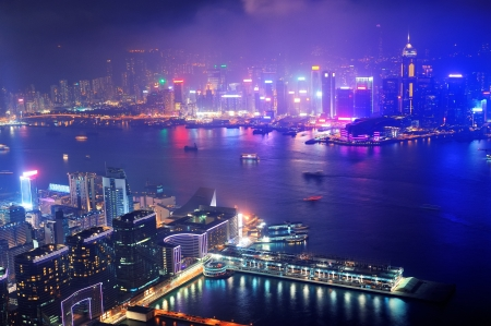 hong kong people: Victoria Harbor aerial view with Hong Kong skyline and urban skyscrapers at night.