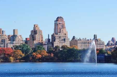 Fountain over lake in New York City Manhattan Central Park with skyscraper buildings and colorful Autumn foliage and clear blue sky. photo