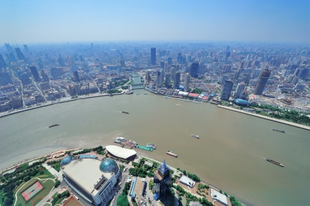 pudong district: Shanghai city aerial view with urban architecture over river and blue sky in the day.