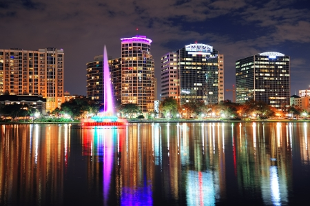 orlando: Orlando downtown skyline over Lake Eola at dusk with urban skyscrapers and lights.