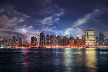 New York City Manhattan midtown panorama at dusk with skyscrapers illuminated over east river photo
