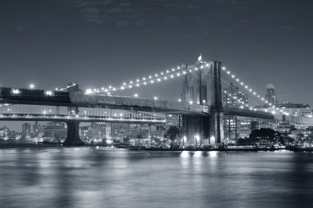 Brooklyn Bridge over East River at night in black and white in New York City Manhattan with lights and reflections