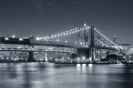 Brooklyn Bridge over East River dans la nuit en noir et blanc dans le New York City Manhattan avec des lumières et des reflets