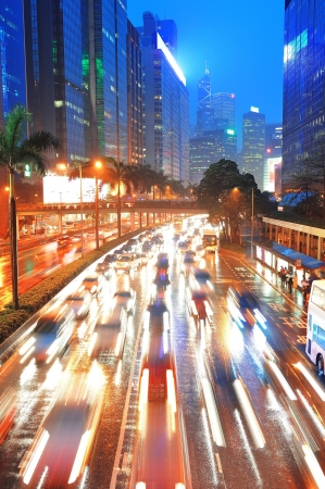 Hong Kong street with busy traffic and skyscraper office at dusk