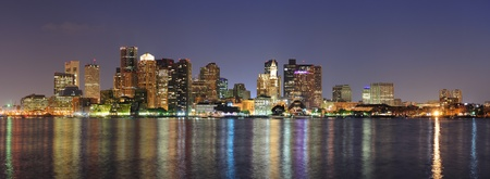 Boston downtown skyline panorama with skyscrapers over water with reflections at dusk illuminated with lights   photo