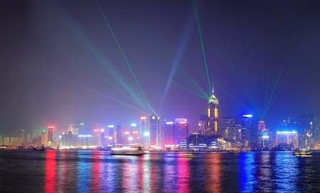 Hong Kong skyline at night with lights and skyscrapers over sea with laser beams photo