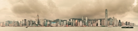 Urban architecture in Hong Kong Victoria Harbor with city skyline and cloud in the day with yellow tone  photo