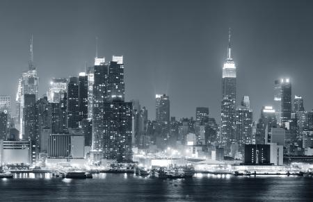 ニューヨーク市ミッドタウン マンハッタンの高層ビルとの夜に黒と白の反射でハドソン川に点灯