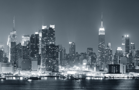 New York City Manhattan midtown skyline black and white at night with skyscrapers lit over Hudson River with reflections   Stock Photo - 14803651