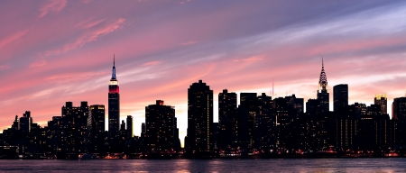 New York City Manhattan midtown silhouette panorama at sunset with skyscrapers and colorful sky over east river photo