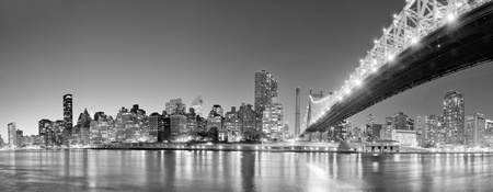 queensboro bridge: Queensboro Bridge over New York City East River black and white at night with river reflections and midtown Manhattan skyline illuminated.