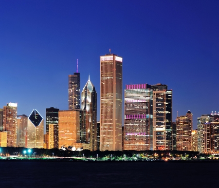 lakefront: Chicago city downtown urban skyline at dusk with skyscrapers over Lake Michigan with clear blue sky.