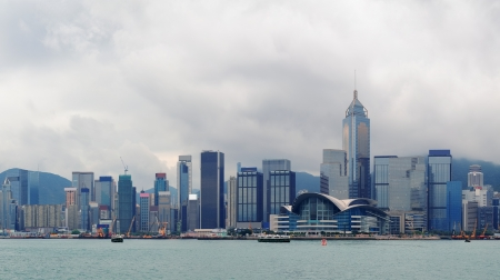 Urban architecture in Hong Kong Victoria Harbor with city skyline and cloud in the day. photo