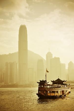 ports: Hong Kong skyline con barche a Victoria Harbor in tono giallo. Archivio Fotografico