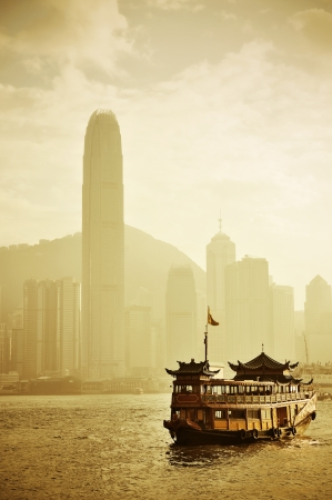 Hong Kong skyline with boats in Victoria Harbor in yellow tone.