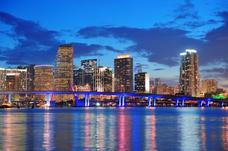 city of miami: Miami city skyline panorama at dusk with urban skyscrapers and bridge over sea with reflection