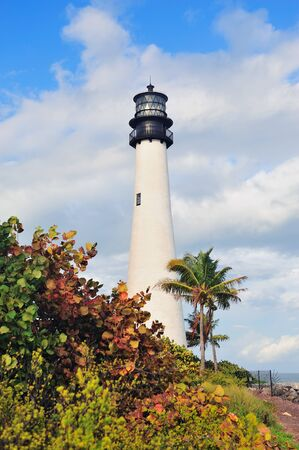 Cape Florida Light lighthouse with Atlantic Ocean and palm tree at beach in Miami with blue sky and cloud. photo