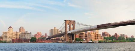 Brooklyn Bridge panorama view over East River viewed from New York City Lower Manhattan waterfront at sunset. photo