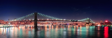 new york at night: Brooklyn Bridge panorama over East River at night in New York City Manhattan with lights and reflections.