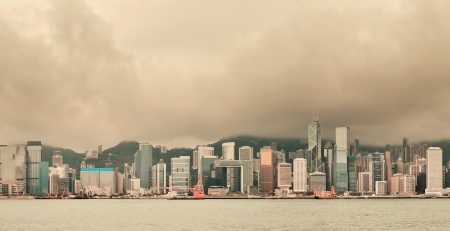 hong kong people: Urban architecture in Hong Kong Victoria Harbor with city skyline and cloud in the day with yellow tone