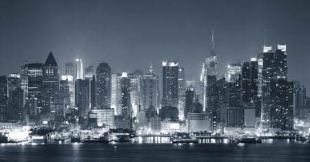 New York City Manhattan midtown skyline black and white at night with skyscrapers lit over Hudson River with reflections   Stock Photo - 15375517