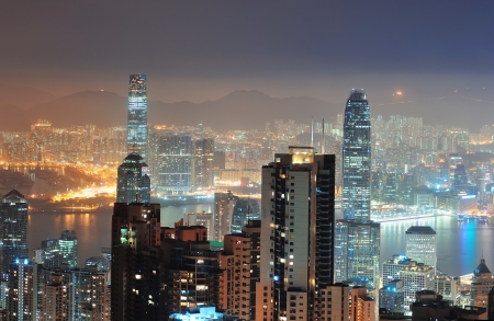 Hong Kong city skyline at night with Victoria Harbor and skyscrapers illuminated by lights over water viewed from mountain top