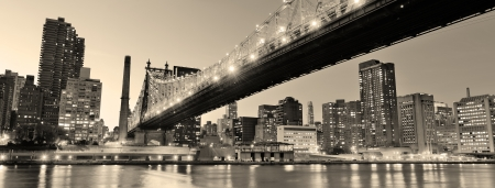 downtown manhattan: Queensboro Bridge over New York City East River black and white at night with river reflections and midtown Manhattan skyline illuminated