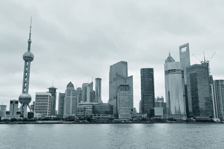 pudong district: Shanghai architecture over river in overcast day in black and white