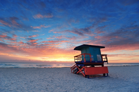miami sunset: Miami South Beach sunrise with lifeguard tower and coastline with colorful cloud and blue sky.