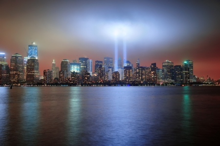 world trade center: New York City Manhattan downtown skyline at night from Liberty Park with light beams in memory of September 11 viewed from New Jersey waterfront.