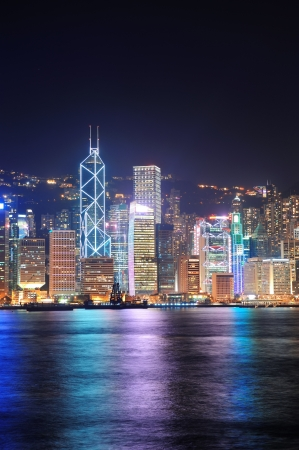 Hong Kong city skyline at night over Victoria Harbor with clear sky and urban skyscrapers. photo