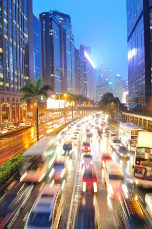 crowded: Hong Kong street with busy traffic and skyscraper office at dusk. Stock Photo