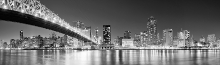 Queensboro Bridge over New York City East River black and white at night with river reflections and midtown Manhattan skyline illuminated