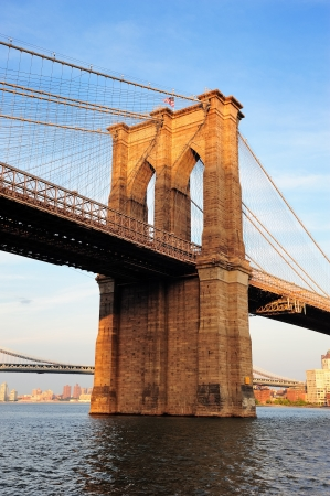 manhattan bridge: Brooklyn Bridge over East River viewed from New York City Lower Manhattan waterfront at sunset. Stock Photo