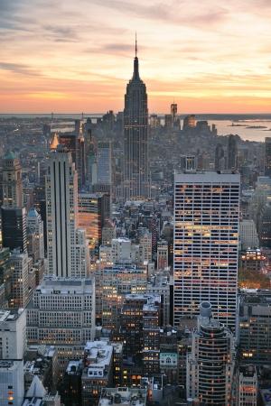 ニューヨーク市のスカイライン眺めカラフルなクラウドとマンハッタンのミッドタウンの高層ビルが夕日に.