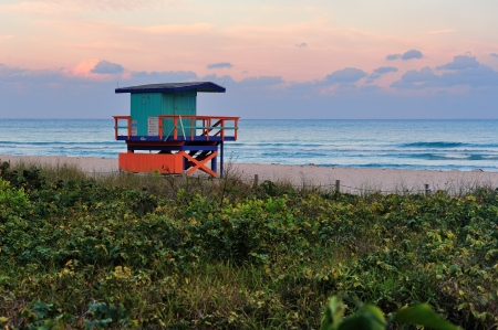 miami south beach: Miami South Beach sunset with lifeguard tower and coastline with colorful cloud and blue sky.
