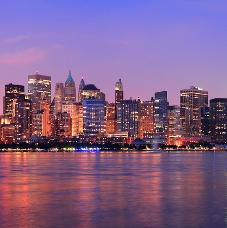 New York City Manhattan downtown skyline at dusk with skyscrapers illuminated over Hudson River panorama photo