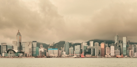 Urban architecture in Hong Kong Victoria Harbor with city skyline and cloud in the day with yellow tone