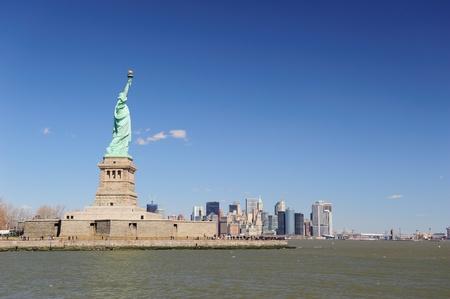 liberty island: Statua della Libert? su Liberty Island e New York City skyline di Manhattan downtown con i grattacieli e cielo blu