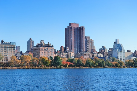 Central Park Autumn with New York City Manhattan Midtown skyline skyscrapers over lake with colorful foliage and clear blue sky. photo